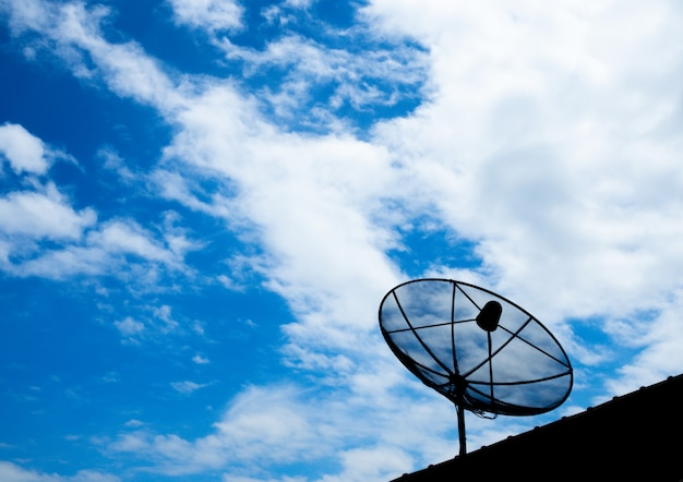Black satellite tv receiver plate on the roof with a blue sky background