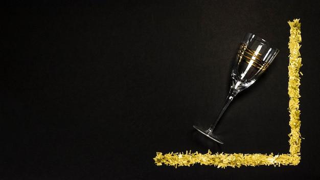 Scena nera, bicchiere di champagne e scintillii