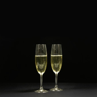 Black scene with two glasses of champagne.