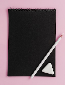 Black scetchbook mockup, white pencil and eraser on pink background.