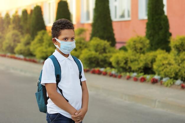 コロナウイルスとインフルエンザの発生時にフェイスマスクを着用した黒人学校の子供。少年はコロナウイルス予防のためにマスクをして学校に戻っています。