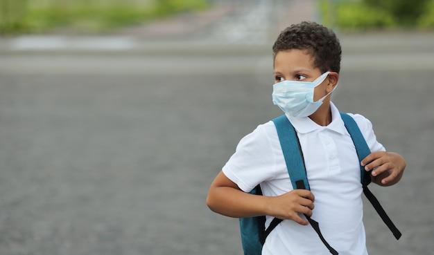 コロナウイルスとインフルエンザ予防のためのフェイスマスクを身に着けている黒い学校の子供。マスクで学校に戻る