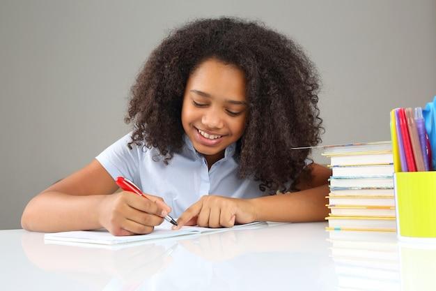 黒人女子校生が宿題をしながらノートに書く