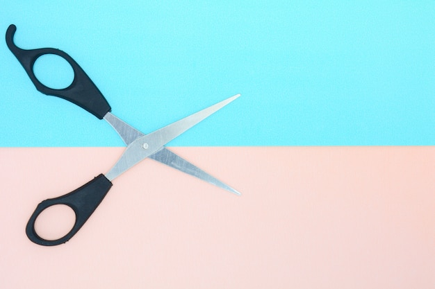 Black scissors on blue and pink paper background