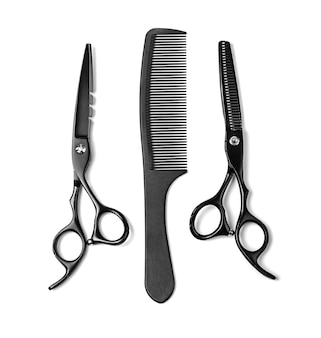 Black scissors iand comb solated on white background
