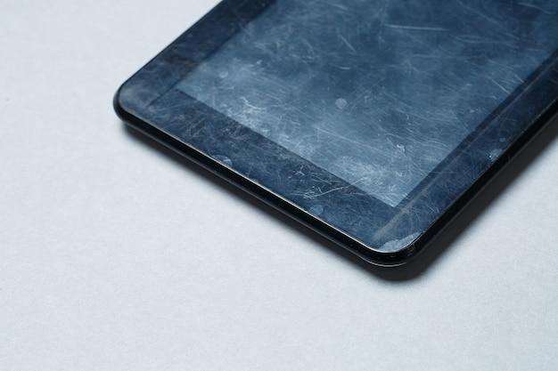 Черный поцарапанный планшет с защитной пленкой на сером фоне. защитите экран вашего устройства
