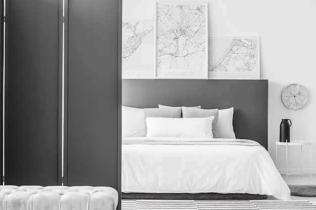 Black screen in minimal hotel room interior with maps above bed next to a clock and table