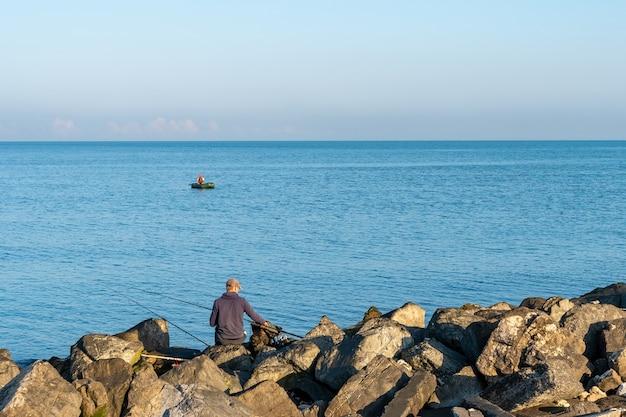 Побережье черного моря в городе поти, рыбак в лодке. грузия