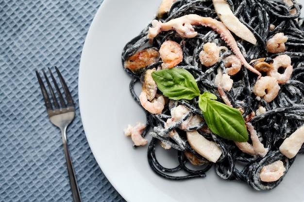 Паста из черных морепродуктов. средиземноморская кухня для гурманов.