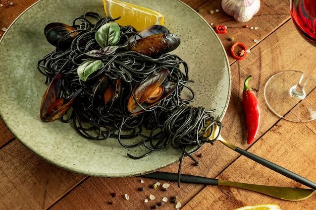 Паста из черных морепродуктов с бокалом красного вина на деревянном столе