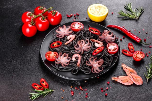 Черная паста из морепродуктов с креветками, осьминогом и мидиями. средиземноморская кухня для гурманов. черная паста с осьминогом на черной каменной плите