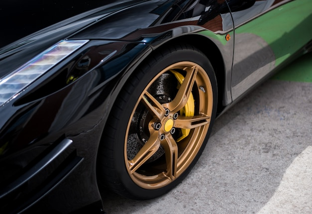 Black sedan car wheel with golden, bronze color decoration.