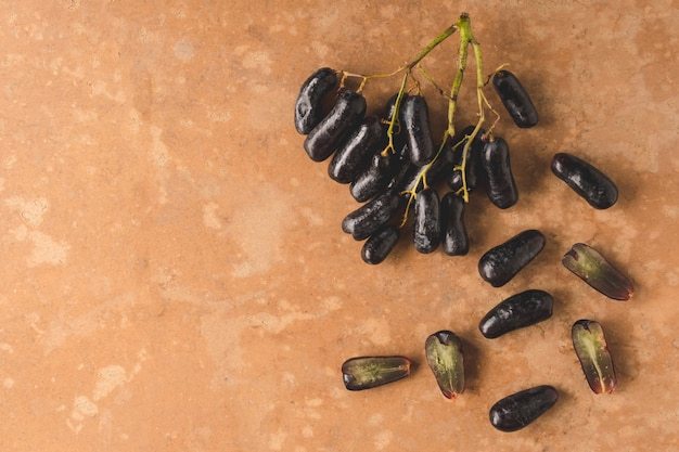 Black seedless moon drops grape or witch fingers grape on brown grunge background.