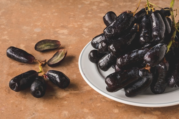 Black seedless moon drops grape or witch fingers grape in white plate