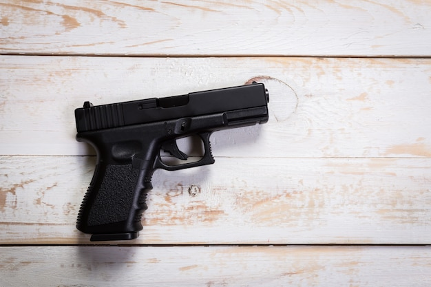 Black semi-automatic gun on old wood .