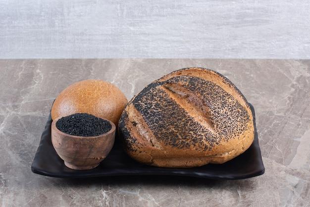 검은 참깨 코팅 빵과 대리석 배경에 플래터에 검은 참깨의 작은 그릇. 고품질 사진