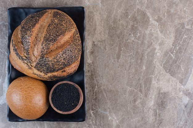 검은 참깨 코팅 빵과 검은 참깨 작은 그릇을 대리석 접시에 담습니다.