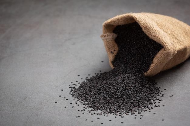 Черный кунжут в мешке на темном фоне