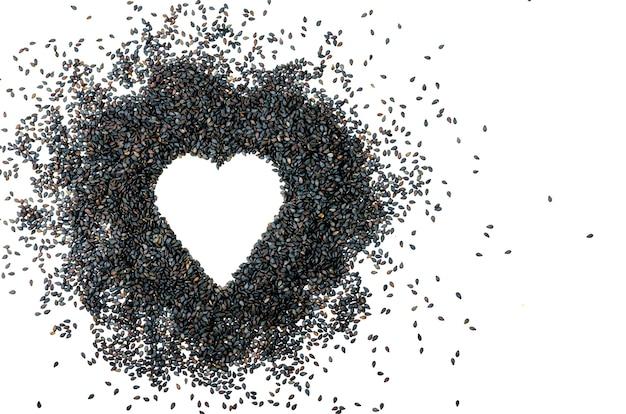 ハートの形をした黒ゴマは、白い背景で隔離されます。健康、健康食品、愛。コンセプト。コピースペース
