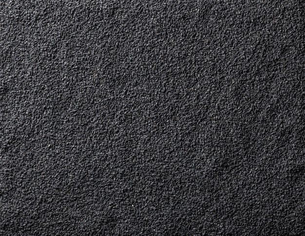 Black sesame seeds background, top view