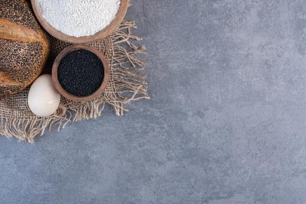 Черные семена кунжута, мука, яйцо и кусок хлеба с кунжутом на мраморном фоне. фото высокого качества