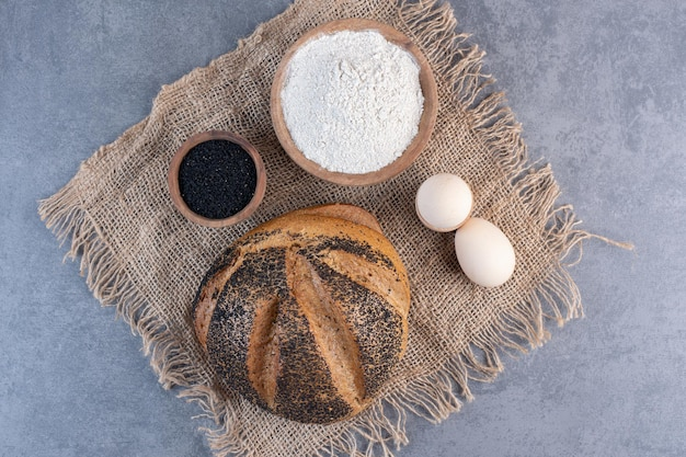 Black sesame seeds, flour, eggs and a sesame coated bread loaf on marble background. high quality photo
