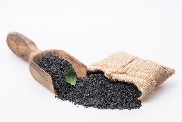 Семена черного кунжута. здоровые семена кунжута в совок и джутовый мешок, изолированные на белом