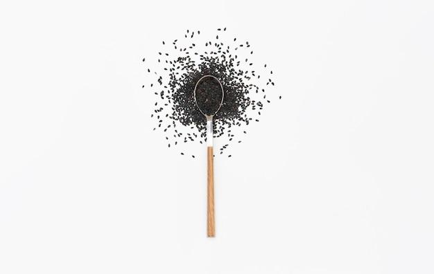 Черные семена кунжута в ложке, изолированные на белом. плоская планировка. вид сверху