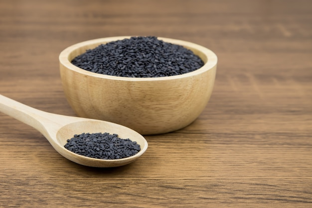 Семена черного кунжута в деревянной ложке