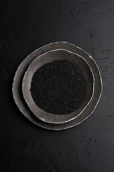 Черные семена кунжута в черных керамических тарелках на темном старом винтажном фоне. деревенский стиль. вид сверху.