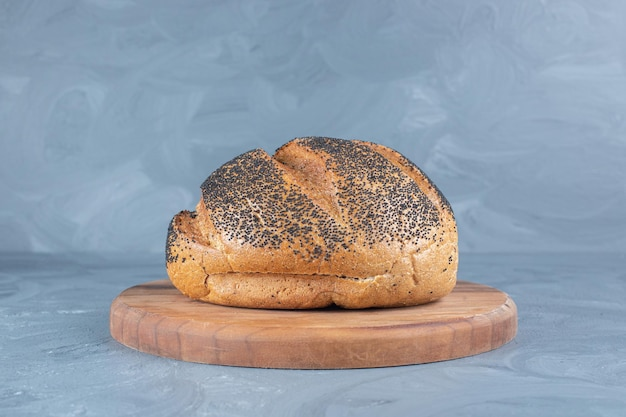 Black sesame seeds on a load of bread of a wooden board on marble background.