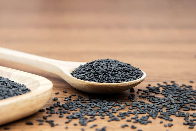 Black sesame seeds in a wooden spoon.