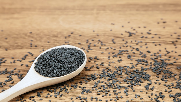 Black sesame seeds in a wooden spoon