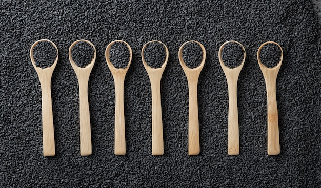 Black sesame seeds in wooden spoons on a background of scattered sesame seeds