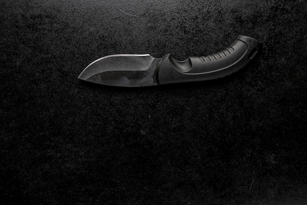 黒いハンドルの黒い鋭い小さなナイフ