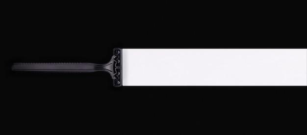 それ自体の後に白い痕跡がある黒い背景に黒いシェービングカミソリ。右側のテキストの空の場所。