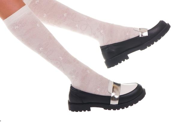 Черные кожаные ботинки девушки блеска изолированные на белизне.