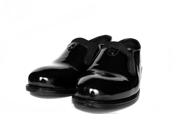 白い背景の上の黒い光沢のあるパテントレザーの靴黒い新しいブーツ