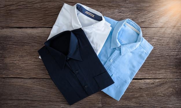 Черная рубашка, рубашка с белой рубашкой и джинсами на деревянном фоне