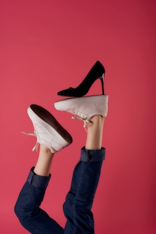 Black shoe on the leg photo of a woman pink background shopping
