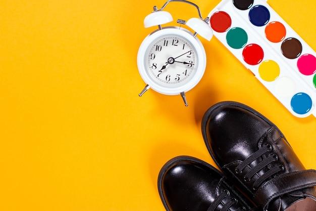 Black shoes alarm clock and paints
