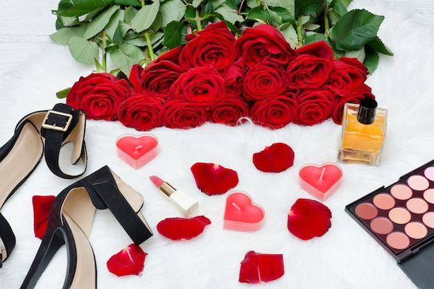 Black shoes and a bouquet of red roses on a white fur. red candles, lipstick and perfume