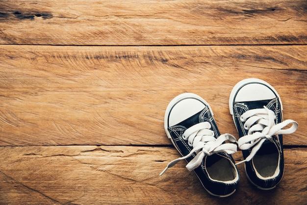 Black shoes for children on wooden floor