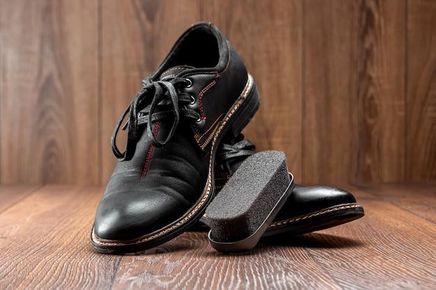 Черные ботинки одна чистая вторая грязная и щетка на деревянной стене. концепция обуви, уход за одеждой, услуги.