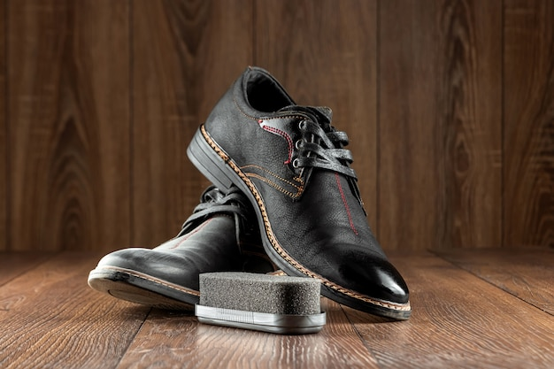 Black shoes one clean second dirty and brush on a wooden wall. the concept of shoe shine, clothing care, services.