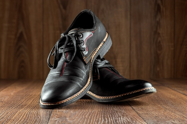 Черные ботинки одна чистая вторая пакостная на деревянной стене. концепция обуви, уход за одеждой, услуги.