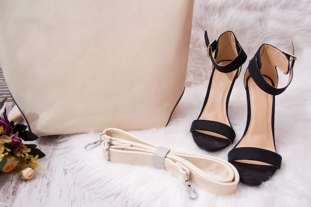 Black shoes, part of a beige women's bag, on white fur. fashionable concept