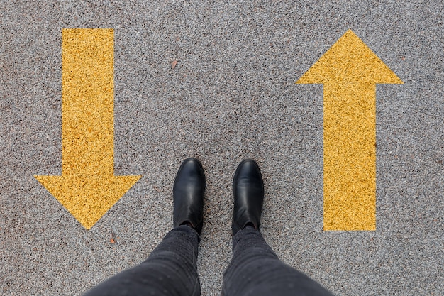 Black shoes standing on the asphalt concrete floor with two yellow arrows.