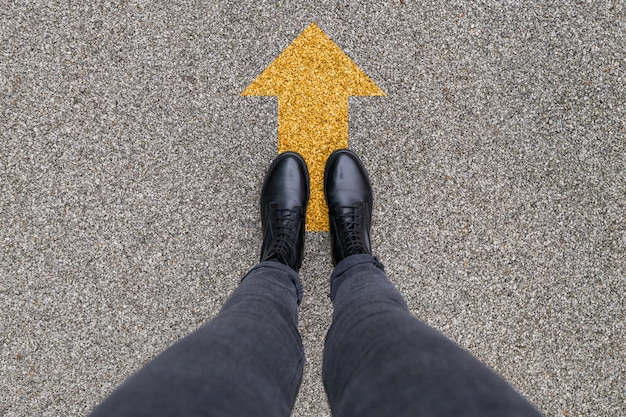 Black shoes standing on the asphalt concrete floor with yellow direction arrow symbol. moving forward, new start and success.. feet shoes walking in outdoor. youth selphie modern hipster