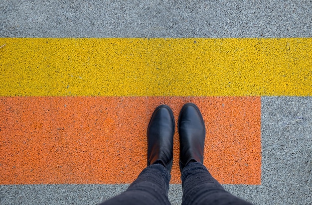 Black shoes standing on the asphalt concrete floor with yellow and orange lines. feet shoes walking in outdoor. youth selphie modern hipster